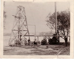Pictured is the first deep artesian well in Rockford.  Rock River is in the background. (History of the Rockford Water Division/Thomas Powers)